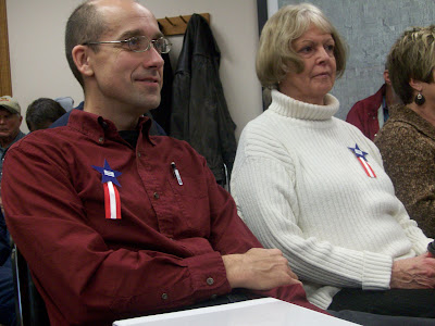 Kalona resident James Graham (left) is among those who donned pins reading Free County at this Week's board of supervisors meeting