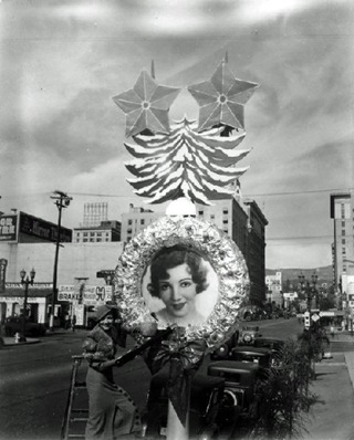 Claudette Colbert next to her image on a Christmas decoration near Hollywood and Vine.
