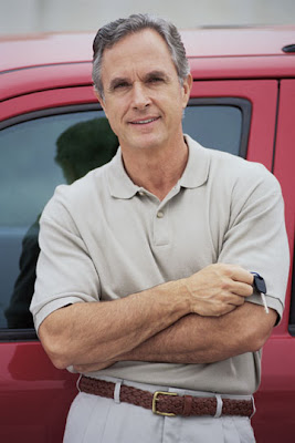 A man standing next to a red pick up truck.