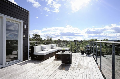 Swedish House With Dark Wooden Exterior And Detached Garage Near By