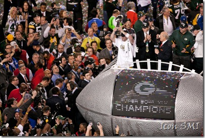 Green Bay Packers QB and Super Bowl MVP Aaron Rodgers #12 holds up the Lombardi Trophy with former NFL QB and Fox Sports broadcaster Terry Bradshaw after the Green Bay Packers defeat Pittsburgh Steelers 31-25 to win Super Bowl XLV at Cowboys Stadium in Arlington, Texas.