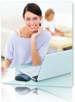 Woman smiling at a computer with a child in the background.