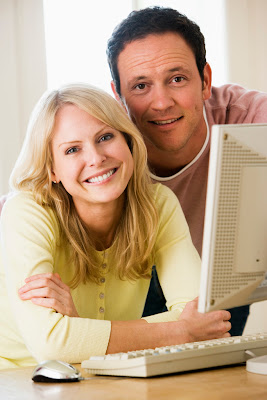 A smiling couple using a computer to apply for bad credit loans online.