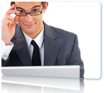 Man lowering eyeglassing to make eye contact over a white laptop.
