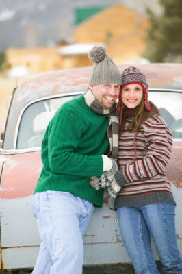 A couple smililng and standing near a newly repaired vehicle.