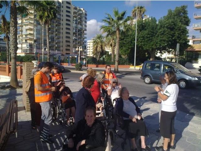 Voluntarios de Protección Civil Benalmádena, ayudando a los mayores en el paseo.