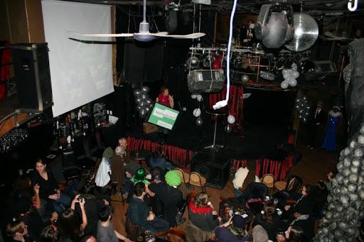 photo de haut de la salle, style bar-spectacle. On voit Maude vêtue un peu glamour avec une affiche Applaudissez! et les deux animateur.trices sur le coin de la scène s'appretant à embarquer.
