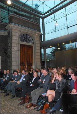 Cabaretier Joop Vos vermaakt het publiek in de Glazen Zaal in Den Haag. Op de voorste rij de sprekers: vlnr Louis Pols (dagvoorzitter), Ewoud Sanders, Henk den Heijer (half achter), Peter Doorn, Willem Bouten, een vertegenwoordiger van NWO, Johan van Rooijen, Esther Jansma en Frank van Harmelen