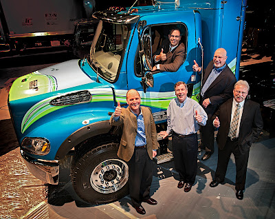 In the driver's seat of compressed natural gas-fueled Business Class M2 is Dave Bryant of Freightliner, and at his left on the ladder is National Truck Equipment Association executive director Jim Carney. Calstart president and CEO John Boesel is at front left. Agility Fuel Systems is the truck's CNG tank assembly provider, and Agility president Ron Eickelman is at center. NTEA business development director Doyle Sumrall gives his thumbs-up at far right.