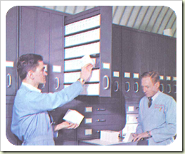 Workers at the GMRV move microfilm masters into storage cabinets