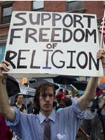 Man holding sign reading 'Support Freedom of Religion'