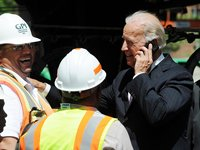Biden talks on phone while construction workers laugh