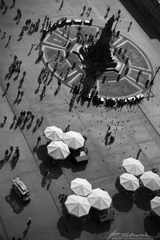Kraków. Widok z Kościoła Mariackiego na Rynek. Podwojone słońcem ludzkie sylwetki przemieszczające sięw każdym możliwym kierunku, obwoźna wyczieczka w melexie, parasole kwiaciarek i panujący nad wszystkim wieszcz.
