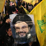 "Lebanese Hezbollah supporters wave the movement's flag as they listen to the party's chief Hassan Nasrallah (poster) giving a televised speech during a festival in southern Beirut on May 25, 2009 to mark the ninth anniversary of Israel's withdrawal from southern Lebanon after a 22-year presence. Nasrallah denounced a report implicating his party in the killing of ex-premier Rafiq Hariri as ""very, very dangerous"" and accused Israel of being behind it. Germany's Der Spiegel news magazine reported on May 23 that the UN commission probing the Hariri murder had new evidence that Hezbollah special forces ""planned and executed"" the Beirut car bombing on February 14, 2005. AFP PHOTO/RAMZI HAIDAR"