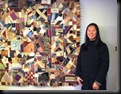 Livia Nufer standing beside the crazy quilt
