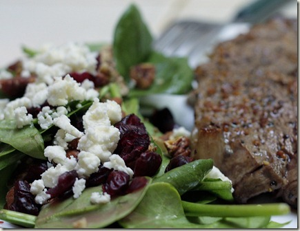 baby spinach salad with dried cranberries, chopped pecans, and feta cheese, drizzled with raspberry vinaigrette