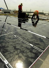 Workers install solar panels on a warehouse rooftop in California. Eventually there will be 33,700 on the structure. Courtesy of Southern California Edison