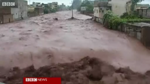 Floodwaters surge through a town in Pakistan, 29 July 2010. BBC News