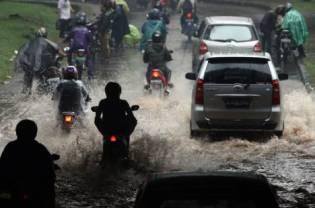 Motorbikes splash through deep puddles of water after heavy rains lashed the Semanggi area of Jakarta on Wednesday, 18 August 2010.JG Photo / Safir Makki