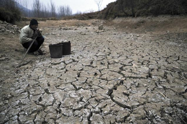 In this photo taken on January 28, 2011, a Chinese farmer smokes near a dried up pond in the village of Danuanzhang in Rizhao in eastern China's Shandong province. Months of dry weather have given China's key wheat-growing province of Shandong its worst drought in at least 40 years. AP