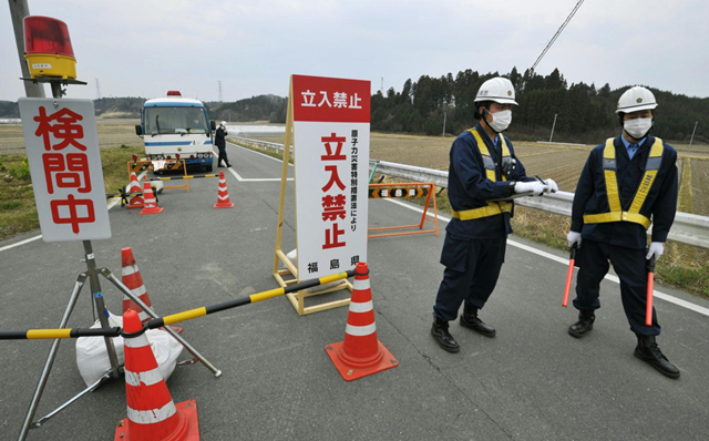 Police officers man a checkpoint in Minamisoma, Fukushima Prefecture, Japan, about 20-kilometers (12-miles) from the tsunami-damaged Fukushima Dai-ichi nuclear power plant Monday, April 11, 2011. The signs read 'No entry, Entry not allowed by the special nuclear disaster legislation,' right, and 'Security check in operation,' left. Kyodo News