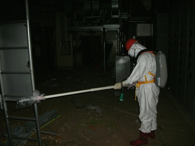 A worker measures radiation levels inside the reactor building of Fukushima Daiichi Nuclear Power Station Unit 1, 5 May 2011. TEPCO