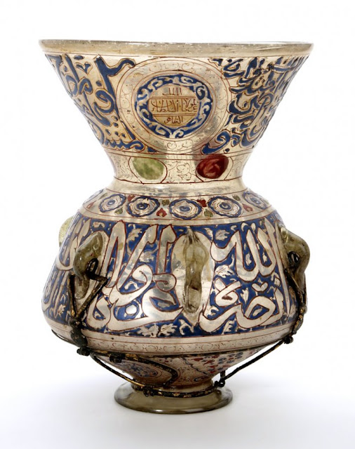 "The rim of this lamp bears an inscription from the surah al-Nur (Light), verse 35: ""God is the Light of the heavens and the earth. The parable of His Light is as if there were a Niche and within it a Lamp: the Lamp enclosed in Glass."" Syria or Egypt. 15th century. 33 x 25 cm. Courtesy of the Nasser D Khalili Collection of Islamic Art."