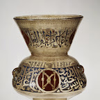 This lamp is the earliest datable example of its kind known to have hung in an interior that still survives. The inscription states that it was made for the tomb of the Mamluk emir Aydakin al-cAla'i al-Bunduqdar (died 1285) in Cairo. The emblem of the Keeper of the Bow, a pair of confronted bows against a red background, appears nine times on this lamp. A rare mistake by the calligrapher is evident on the neck, where the word bunduqdar (Keeper of the Bow) has been misspelled as a meaningless word, bunqud-dar.