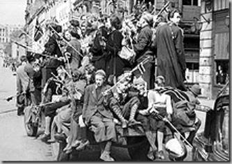 """Oslo 8 mai 1945.  Den andre verdenskrig (1940-45) er over og frigjøringsfesten er igang i Oslo. Unge og gamle har besatt lastebiler av alle slag og kjører rundt i gatene. En norsk politimann har overtatt trafikkdirigeringen på Karl Johansgate mens en """"slagen"""" tysk soldat bivåner det hele.SCANPIX/Arkiv."""
