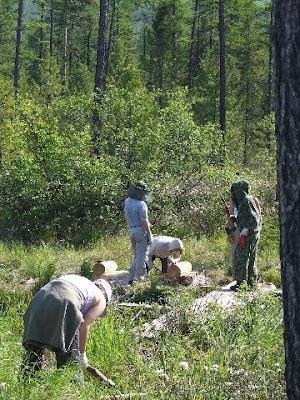 Während im Hindergrund das Fundament der Nordpylone ausgerichtet wird, schält die kleine Tanja Rinde von einem Stamm.