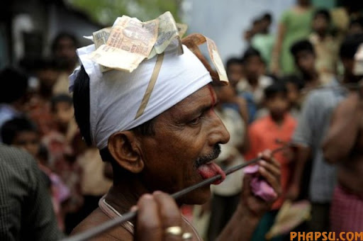 An Indian Hindu devotee adjusts a metal rod pierced through his tongue during the ritual of Shiva Gajan at a village in Bainan, some 80 kms south of Kolkata, on April 14, 2010. Devotees believe that by enduring the pain, Shiva, the Hindu god of destruction, will grant their prayers. Thousands took part in the month-long festival which culminates with the worship of Shiva on the auspicious day of Chaitra Sankranti, the last day of the Bengali calendar year.    AFP PHOTO/Deshakalyan CHOWDHURY (Photo credit should read DESHAKALYAN CHOWDHURY/AFP/Getty Images)