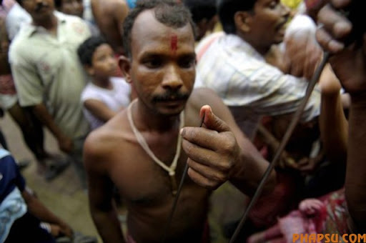 An Indian Hindu devotee checks the tip of a metal rod before using it to pierce his tongue during the ritual of Shiva Gajan at a village in Bainan, some 80 kms south of Kolkata, on April 14, 2010. Devotees believe that by enduring the pain, Shiva, the Hindu god of destruction, will grant their prayers. Thousands took part in the month-long festival which culminates with the worship of Shiva on the auspicious day of Chaitra Sankranti, the last day of the Bengali calendar year.    AFP PHOTO/Deshakalyan CHOWDHURY (Photo credit should read DESHAKALYAN CHOWDHURY/AFP/Getty Images)