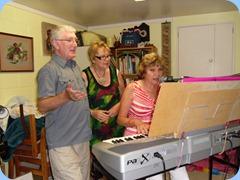 Gordon Sutherland and Jessyka Stuart singing along with Carole Littlejohn