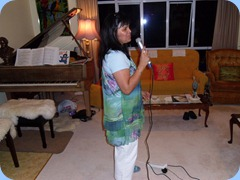 Co-host, Lizza Littlejohn, singing Karaeoke style after dinner. Joint winners of the competition were Lizza and Michael Bramley.