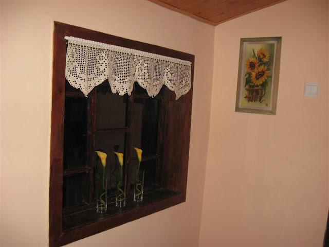 szydełkowa firaneczka zawieszona w oknie ganku na działce