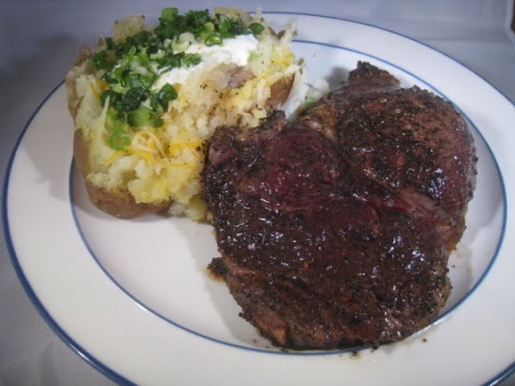 Coffee Crusted Rib eye alongside a Baked Potato