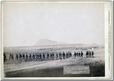"Title: Company ""C,"" 3rd U.S. Infantry, caught on the fly, near Fort Meade. Bear Butte in the distance Thirty five soldiers walking in a line with rifles. 1890. Repository: Library of Congress Prints and Photographs Division Washington, D.C. 20540"