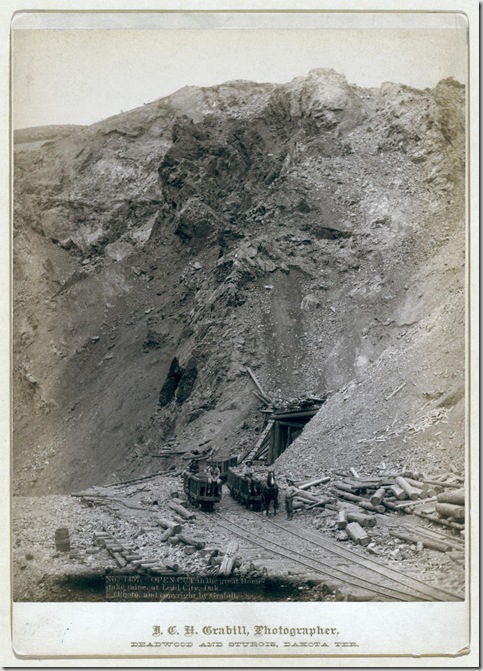 Title: Open cut in the great Homestake mine, at Lead City, Dak. Distant view of mine entrance; four men posed on or near three mining cars on tracks. 1888. Repository: Library of Congress Prints and Photographs Division Washington, D.C. 20540