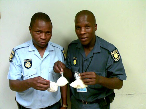 cop poses with drugs