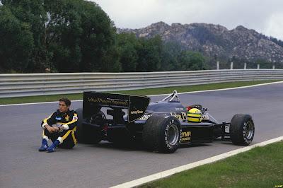 Айртон Сенна сидит около своего Lotus на треке в Эшториле на Гран-при Португалии 1985