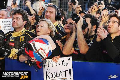 Оксана Косаченко вместе с механиками Lotus Renault у подиуме Гран-при Австралии 2011 с надписью We Miss You Robert