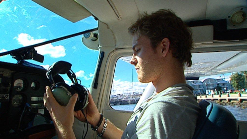 Нико Росберг примеряет наушники пилота перед полетом на самолете над Мельбурном