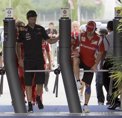 Марк Уэббер и Фернандо Алонсо преодолевающий турникет на Гран-при Малайзии 2011