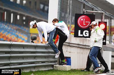 Адриан Сутиль и Нико Хюлькенберг с механиками перелазят защитное ограждение на Гран-при Турции 2011