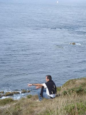 岬のふちに座って海を指さす人