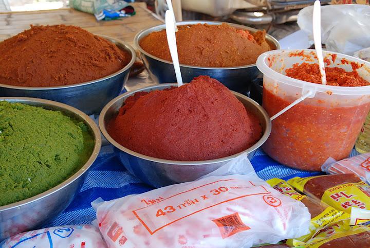 Разноцветные пасты кари на рынке, Таиланд