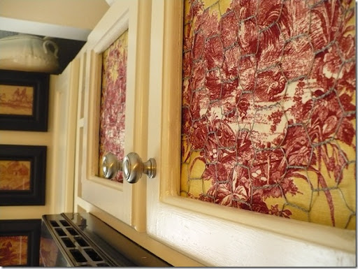 Closeup Of A Kitchen Cabinet With Chicken Wire And Toile Fabric