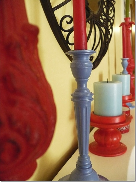colorful candlesticks and candles on a fireplace mantle