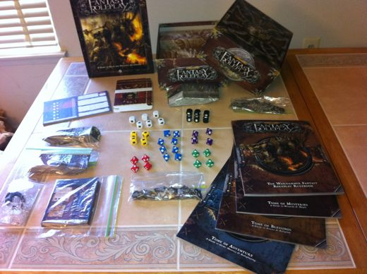 [Image: The Warhammer Fantasy Roleplay kit, splayed out across my table like a train wreck. Contains four books; scads of cards for skills, abilities, insanities, professions, and conditions; stand-ups for the included professions, and 36 custom dice. That is a lot of stuff to pack into a game that can only accommodate three players at a time without buying an expansion.]