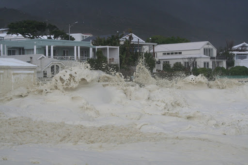 Waves and foam harassing houses in Bakoven, Cape Town